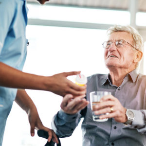 Nurse handing a glass of water to a smiling elderly man